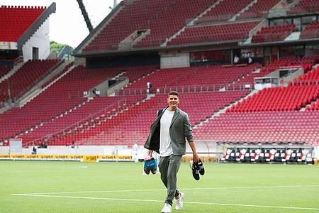 Mario Gomez hat seine Fußballschuhe ausgezogen und verlässt das Spielfeld. Foto: Tom Weller/dpa
