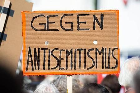 Ein Person hält bei einer Kundgebung gegen Antisemitismus ein Plakat in die Höhe. Die Erfassung antisemitischer Straftaten soll verbessert werden - dafür wollen sich Baden-Württemberg und Nordrhein-Westfalen auf der am Mittwoch beginnenden Innenministerkonferenz einsetzen. Foto: Christophe Gateau/dpa