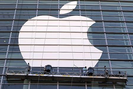 Arbeiter bringen ein übergroßes Apple-Logo an einer Glasfassade in San Francisco an. Foto: Christoph Dernbach/dpa
