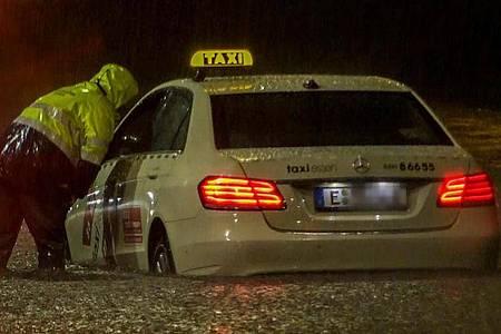 In Essen kam ein Taxi nach einem Starkregen-Guss und einer nachfolgenden Überschwemmung nicht mehr vomFleck - die Feuerwehr versuchte zu helfen. Foto: Markus Gayk/TNN/dpa