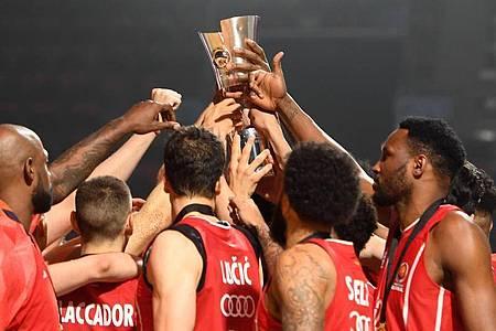 Das Team des FC Bayern reckt den Pokal in die Höhe. Foto: Tobias Hase/dpa