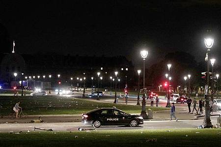 Ein Polizeifahrzeug patrouilliert in der Nähe von Les Invalides am frühen Morgen, nachdem sich Menschen am Freitagabend zu einer nicht genehmigten Party versammelt hatten. Foto: Geoffroy Van Der Hasselt/AFP/dpa