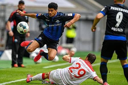 Markus Suttner geht robust gegen den Paderborner Mohamed Dräger (l) in den Zweikampf. Foto: Sascha Schuermann/AFP-Pool/dpa