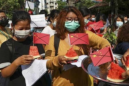 Anti-Putsch-Demonstranten tragen während eines Protests Wassermelonenstücke, in denen durchgestrichene chinesische Fähnchen stecken. Foto: --/AP/dpa