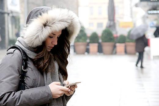 Frau mit Kapuze schaut auf ihr Smartphone
