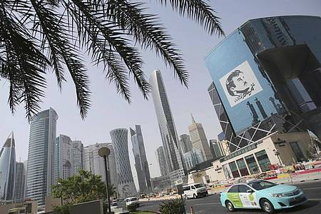 Ein Taxi fährt in Doha an einem Gebäude mit einem Bild des Emirs von Katar, Tamim bin Hamad Al Thani, vorbei. Der Streit zwischen Katar und seinen Nachbarn ist beigelegt. Foto: Kamran Jebreili/AP/dpa