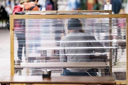 Gäste eines Restaurants warten zwischen Plexiglas-Trennscheiben auf ihre Bestellung. In Hamburg gilt ab dem Wochenende die sogenannte 2G Regelung. Foto: Axel Heimken/dpa