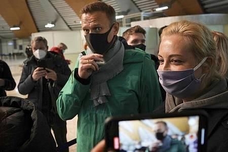 An der Passkontrolle ist Kremlkritiker Alexej Nawalny (M) - hier mit seiner Frau Julia - abgeführt worden. Foto: Mstyslav Chernov/AP/dpa