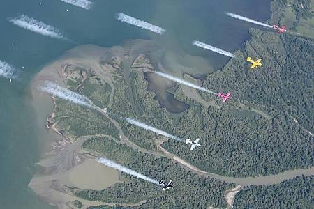 Fünf Kleinflugzeuge fliegen parallel über den Chiemsee. Beim «Schreiben» hilft ein Computersystem. Foto: Dietmar Schreiber/www.airtoair.at/dpa