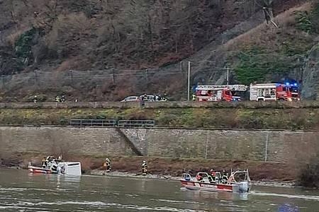 Einsatzkräfte von Feuerwehr und Wasserschutzpolizei kümmern sich um das im Rhein treibende Wohnmobil. Foto: -/Wasserschutzpolizei/dpa