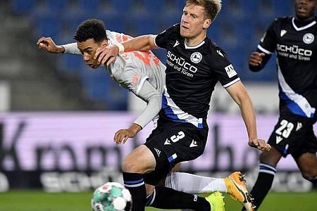 Jamal Musiala (l) von Bayern in Aktion gegen Brian Behrendt (M) von Bielefeld. Foto: Martin Meissner/AP-Pool/dpa