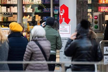 Passanten stehen Schlange vor einer Apotheke. Menschen, die vollständig gegen das Coronavirus geimpft sind, können sich ab heute in Apotheken einen digitalen Impfnachweis abholen. Foto: Julian Stratenschulte/dpa