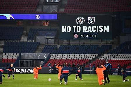 Die Spieler von Paris Saint-Germain und Istanbul Basaksehir sowie die Schiedsrichter knien vor dem Champiopns-League-Spiel als Zeichen der Solidarität mit der Anitrassimus-Bewegung nieder. Foto: Franck Fife/AFP/dpa