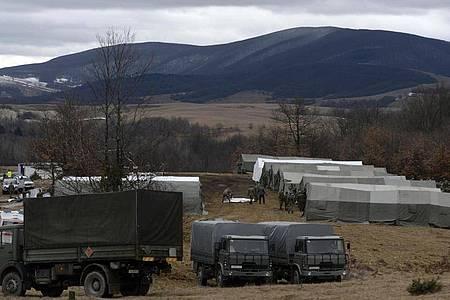 Bosnische Soldaten stehen vor provisorischen Zelten im Camp Lipa außerhalb von Bihac. Nach der gescheiterten Verlegung von Hunderten Flüchtlingen in feste Unterkünfte im Landesinneren hat die bosnische Armee damit begonnen, im Elendslager Lipa im Nordwesten des Landes Zelte zu errichten. Foto: Kemal Softic/AP/dpa