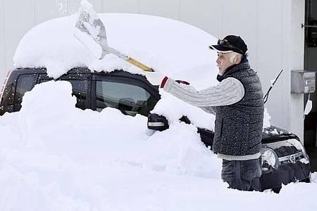 Völlig bedeckt von Neuschnee:Ein Mann in Fukui schaufelt sein Auto frei. Foto: --/kyodo/dpa