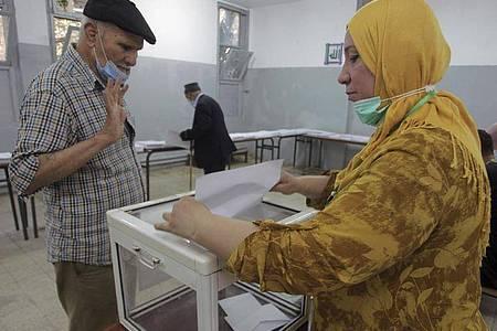 Ein Mann gibt in einem Wahllokal in Algier seine Stimme ab. Foto: Fateh Guidoum/AP/dpa
