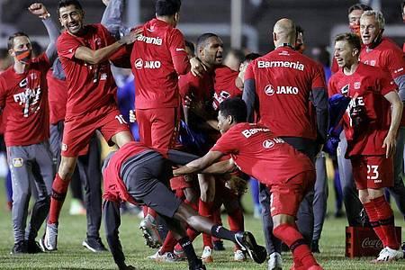 Die Spieler von Bayer Leverkusen feiern den Einzug ins Finale des DFB-Pokals. Foto: Ronald Wittek/epa-Pool/dpa