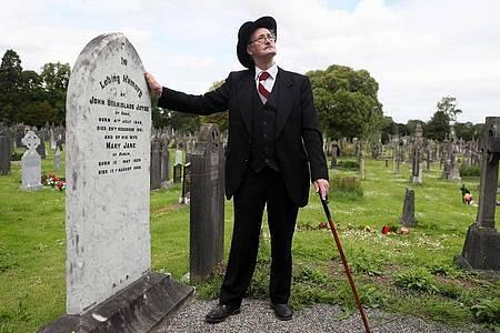 Ein James-Joyce-Darsteller am Grab des Schriftstellers James Joyce und seiner Frau in Dublin (2019). Foto: Brian Lawless/PA Archive/dpa