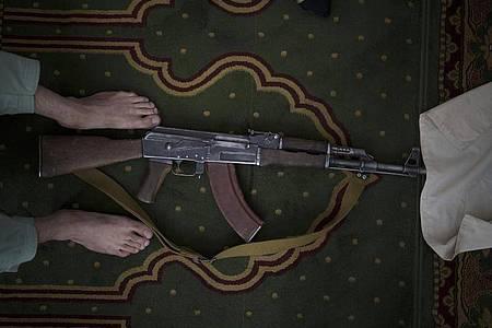 Ein Taliban-Kämpfer nimmt seine Kalaschnikow von Typ AK-47 zum Beten mit in eine Moschee. Foto: Felipe Dana/AP/dpa