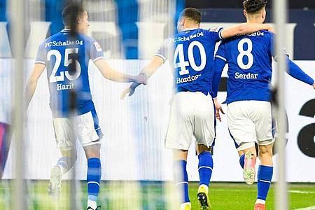 Schalkes Torschütze Suat Serdar (r-l), Can Bozdogan und Amine Harit jubeln über Serdars Treffer zum 1:0. Foto: Bernd Thissen/dpa