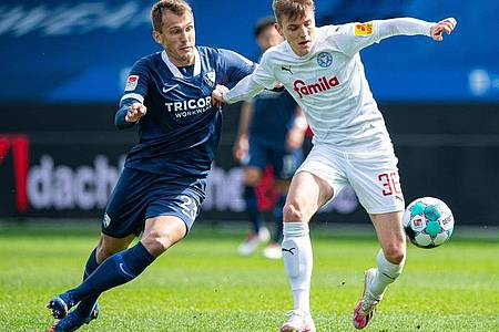 Kiels Niklas Hauptmann (r) und Bochums Robert Tesche kämpfen um den Ball. Foto: Guido Kirchner/dpa