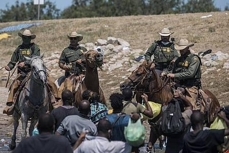 Beamte der US-Zoll- und Grenzschutzbehörde auf Pferden versuchen, Migranten bei der Überquerung des Rio Grande von Ciudad Acuna nach Del Rio aufzuhalten. Foto: Felix Marquez/AP/dpa