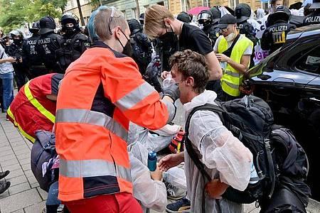 Protestteilnehmer werden von Sanitätern versorgt. Foto: Peter Kneffel/dpa