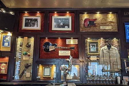Die Gitarren von Eric Clapton (oben rechts) und Pete Townshend (M) waren die ersten im Hard Rock Cafe London. Foto: Philip Dethlefs/dpa