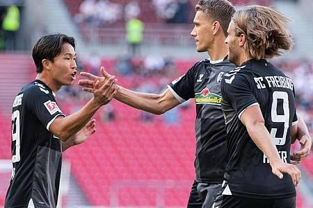 Freiburgs Nils Petersen (M) jubelt nach seinem Tor zum 1:0 mit Wooyeong Jeong (l) und Lucas Höler über den Treffer. Foto: Tom Weller/dpa