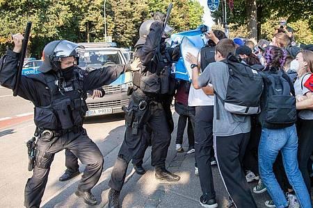 Ein Polizist hebt vor einer Gruppe von Demonstranten seinen Schlagstock. Foto: Peter Kneffel/dpa