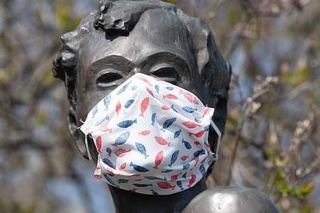 Eine selbstgebastelte Mundschutzmaske über der Kästner-Bronzeplastik in Dresden. Ingenieuren zufolge haben Staubsaugerbeutel für eine Maske der Marke Eigenbau hervorragende Filtereigenschaften. Foto: Sebastian Kahnert/dpa-Zentralbild/dpa