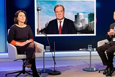 Unions-Kanzlerkandidat Armin Laschet wird auf einem Fernsehschirm gezeigt, während die Mitbewerbern von Grünen und SPD, Annalena Baerbock und Olaf Scholz im Fernsehstudio bei einer Diskussionsrunde des WDR-Europaforums in Berlin sitzen. Foto: Oliver Ziebe/WDR/dpa