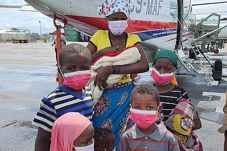 Eine Familie steht auf dem Rollfeld des Flughafens der Provinzhauptstadt Pemba, nachdem sie evakuiert wurden. In der Provinz Cabo Delgado verüben islamistische Rebellen seit 2017 immer wieder brutale Attacken. Nach Angaben des Welternährungsprogramms (WFP) sind in der Region fast eine Million Menschen infolge von Terror und Gewalt vom Hunger bedroht. Foto: Dave Lepoidevin/Ambassador Aviation/AP/dpa