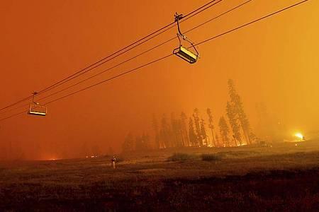 Ein Skilift im Skigebiet Sierra-at-Tahoe vor dem Hintergund des Caldor-Feuers. Foto: Noah Berger/AP/dpa