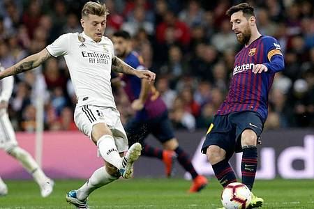 Auch für Toni Kroos (l) und Lionel Messi soll in Spanien der Ball bald wieder rollen. Foto: Andrea Comas/AP/dpa