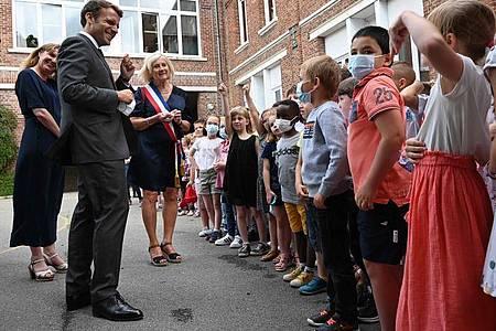 Emmanuel Macron spricht mit Schülerinnen und Schülern einer Grundschule zum Abschluss eines eintägigen Besuchs in Nordfrankreich. Foto: Denis Charlet/AFP/dpa