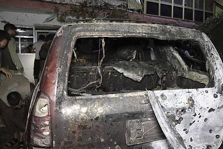 Personen betrachten ein ausgebranntes Fahrzeug in Kabul, das bei einem amerikanischen Drohnenangriff ins Visier genommen wurde. Foto: Khwaja Tawfiq Sediqi/AP/dpa