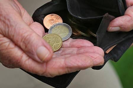 Eine Rentnerin hält einen Geldbeutel mit verschiedenen Euromünzen (gestellte Szenen). Wissenschaftler haben die Politik aufgefordert, vor den Problemen bei der Finanzierung der Rentenversicherung nicht die Augen zu verschließen. Foto: Karl-Josef Hildenbrand/dpa