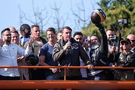 Brasiliens Präsident Jair Bolsonaro sprich nach einer Motorradrallye in Sau Paulo zu seinen Anhängern. Weil er erneut ohne Maske unterwegs war, wurde er von der Landesregierung eines politischen Widersachers mit einer Geldbuße bestraft. Foto: Lincon Zarbietti/dpa