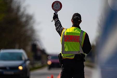 Ein Polizeibeamter kontrolliert hinter der Landesgrenze von Niedersachsen die Zufahrt nach Mecklenburg-Vorpommern. Foto: Philipp Schulze/dpa