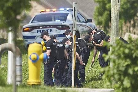 Polizisten in Reihe untersuchen den Tatort eines Autounfalls in London, Ontario. Nach einem Angriff mit einem Auto, bei dem vier Menschen aus einer muslimischen Familie getötet worden sind, geht die Polizei Berichten zufolge von einem rassistischen Tatmotiv aus. Foto: Geoff Robins/The Canadian Press via AP/dpa