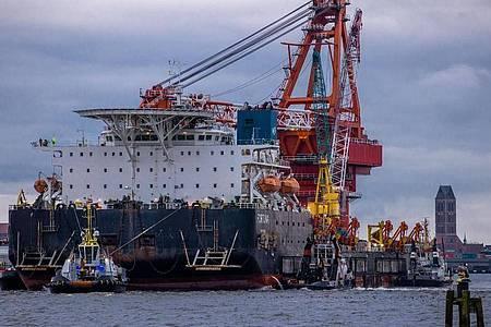 Schlepper ziehen das russische Rohr-Verlegeschiff «Fortuna» aus dem Hafen auf die Ostsee. Foto: Jens Büttner/dpa-Zentralbild/ZB