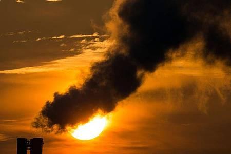 Die Morgensonne hinter qualmenden Schornsteinen eines Blockheizkraftwerkes. Foto: Patrick Pleul/dpa