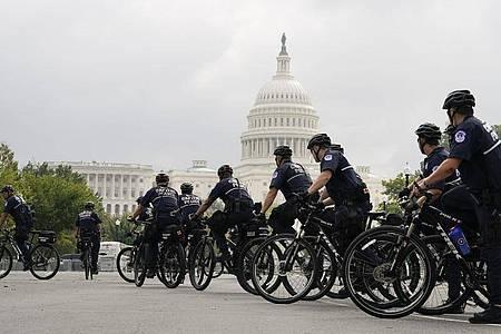 Polizisten auf Fahrrädern beobachten eine Kundgebung in der Nähe des Kapitols. Foto: Jose Luis Magana/AP/dpa