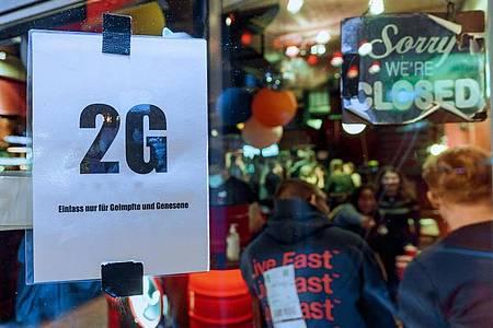 Im Fenster einer Kneipe hängt ein Zettel mit dem Text «2G, Einlass nur für Geimpfte und Genesene». Foto: Markus Scholz/dpa