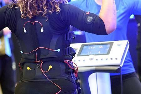 Bei EMS-Training tragen Sportlerinnen und Sportler eine verkabelte Weste und Manschetten, über die elektronische Impulse an den Körper weitergeleitet werden. Foto: Henning Kaiser/dpa-tmn