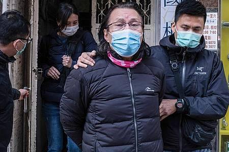 Daniel Wong Kwok-tung (l), Bezirksrat und Anwalt aus dem Stadtteil Kowloon in Hongkong, wird von Polizisten aus seinem Büro eskortiert. Foto: Isaac Wong/SOPA Images via ZUMA Wire/dpa