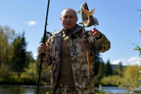 Auch in diesemJahr wieder unter denMotiven aus Putins Sommerurlaub: Russlands Präsident mit Fisch an der Angel. Foto: Alexei Druzhinin/Pool Sputnik Kremlin/AP/dpa
