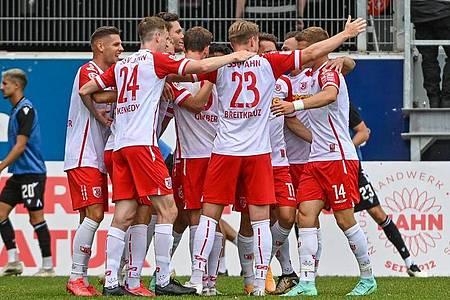 Die Mannschaft von Regensburg feiert den Führungstreffer gegen Sandhausen. Foto: Armin Weigel/dpa