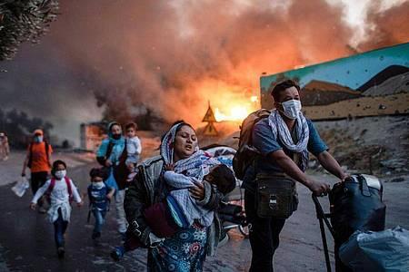 Migranten fliehen vor einem großen Feuer mit ihren Habseligkeiten aus dem Flüchtlingslager Moria. Foto: Petros Giannakouris/AP/dpa